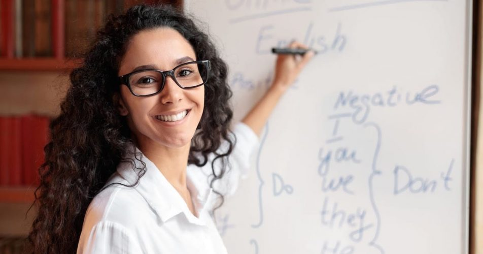 smiling-female-teacher-with-curly-hair-writing-on-the-white-board